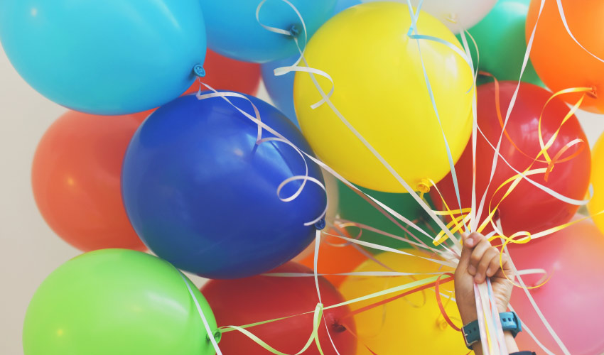 A hand with a blue wristwatch holds a cluster of blue, yellow, green, red, and orange Welcome balloons
