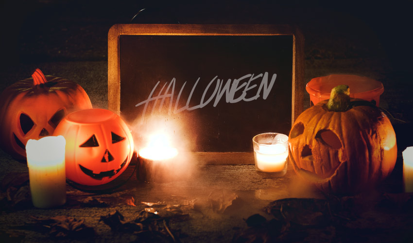 Black chalkboard sign with Halloween written on it surrounded by jack-o-lanterns, candles, and dead leaves