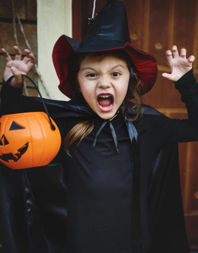 Brunette girl dressed up as a witch while holding an orange pumpkin container