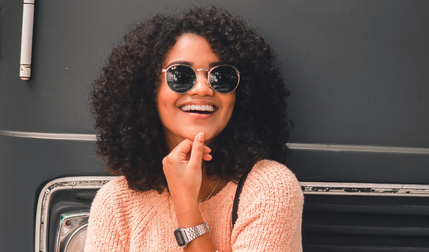 Curly-haired woman wearing sunglasses, peach sweater, and a silver watch smiles with veneers