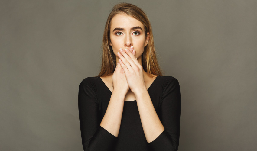 Blonde woman wearing a black shirt covers her mouth due to a white film on her tongue