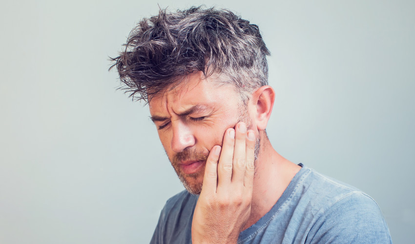 Middle-aged man in a gray shirt winces and touches his cheek due to an emergency toothache