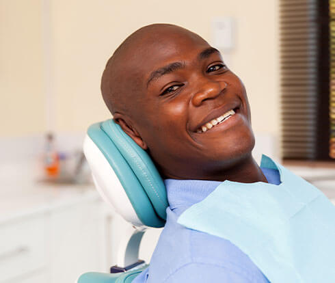 Man sitting in dental exam chair waiting for his root canal procedure