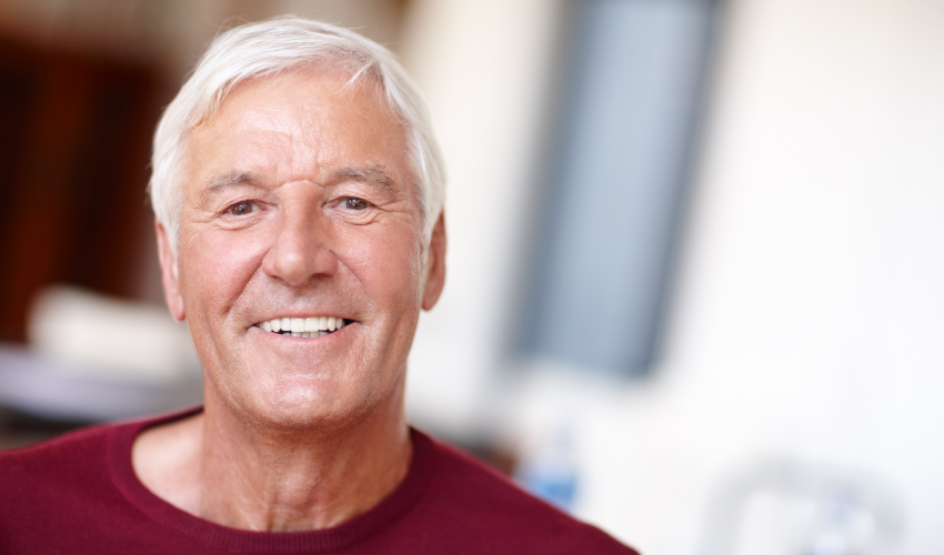 White-haired man wearing a red shirt smiles with his dentures