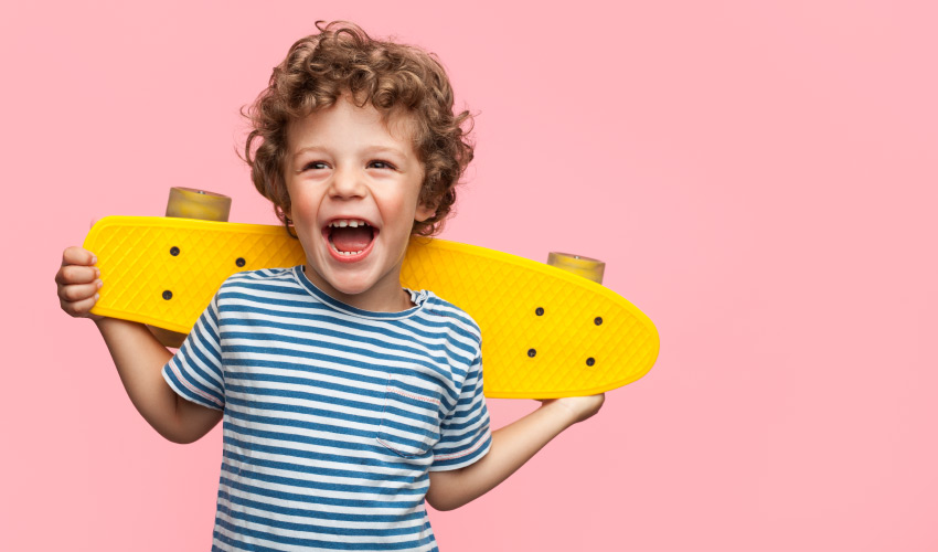 Brunette boy holding a yellow skateboard against a pink wall smiles while laughing