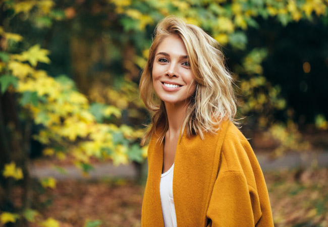 Blonde woman wearing a mustard-colored jacket in the fall smiles with her dental implants