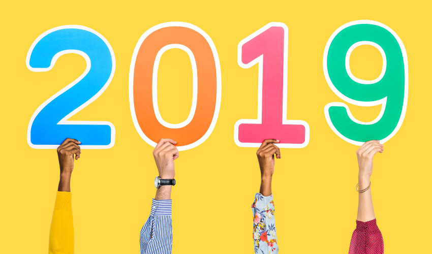 4 hands hold up multicolored 2019 numbers for our Bethea Family Dentistry year in review blog post