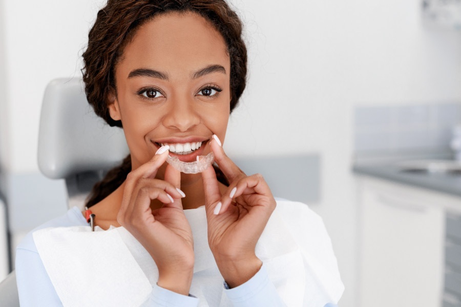 Pretty smiling black girl holding an Invisalign clear aligner in the dentist office