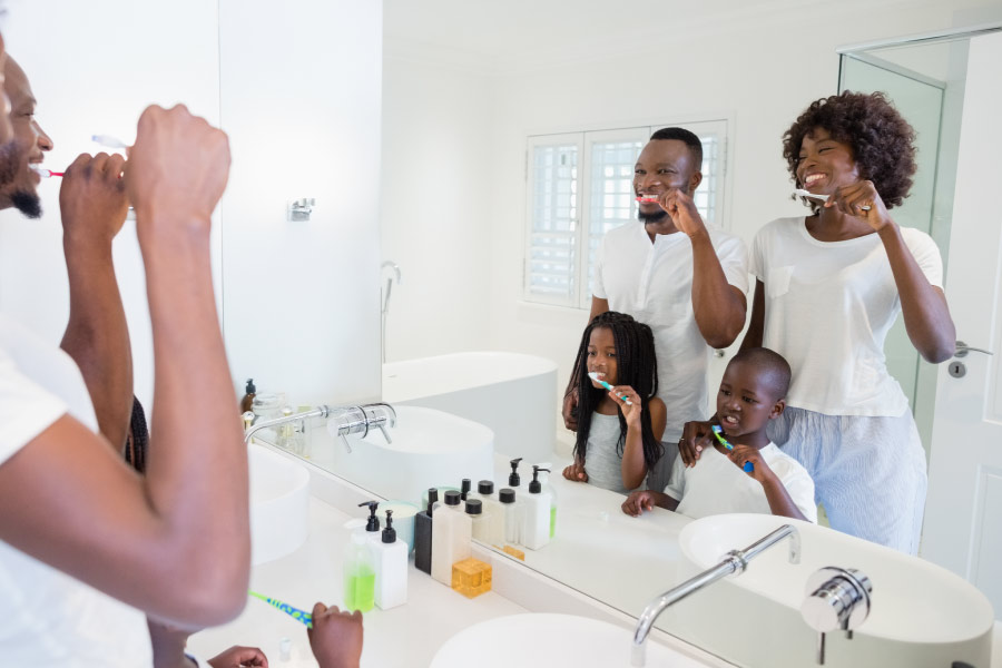 Reflection in bathroom mirror of a black family brushing their teeth with a mom, dad, young son & daughter