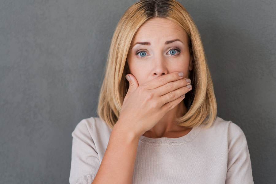 Blonde woman covering her mouth with her hand because of concern about bad breath.